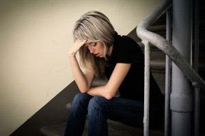 Depressed woman sitting on stairs